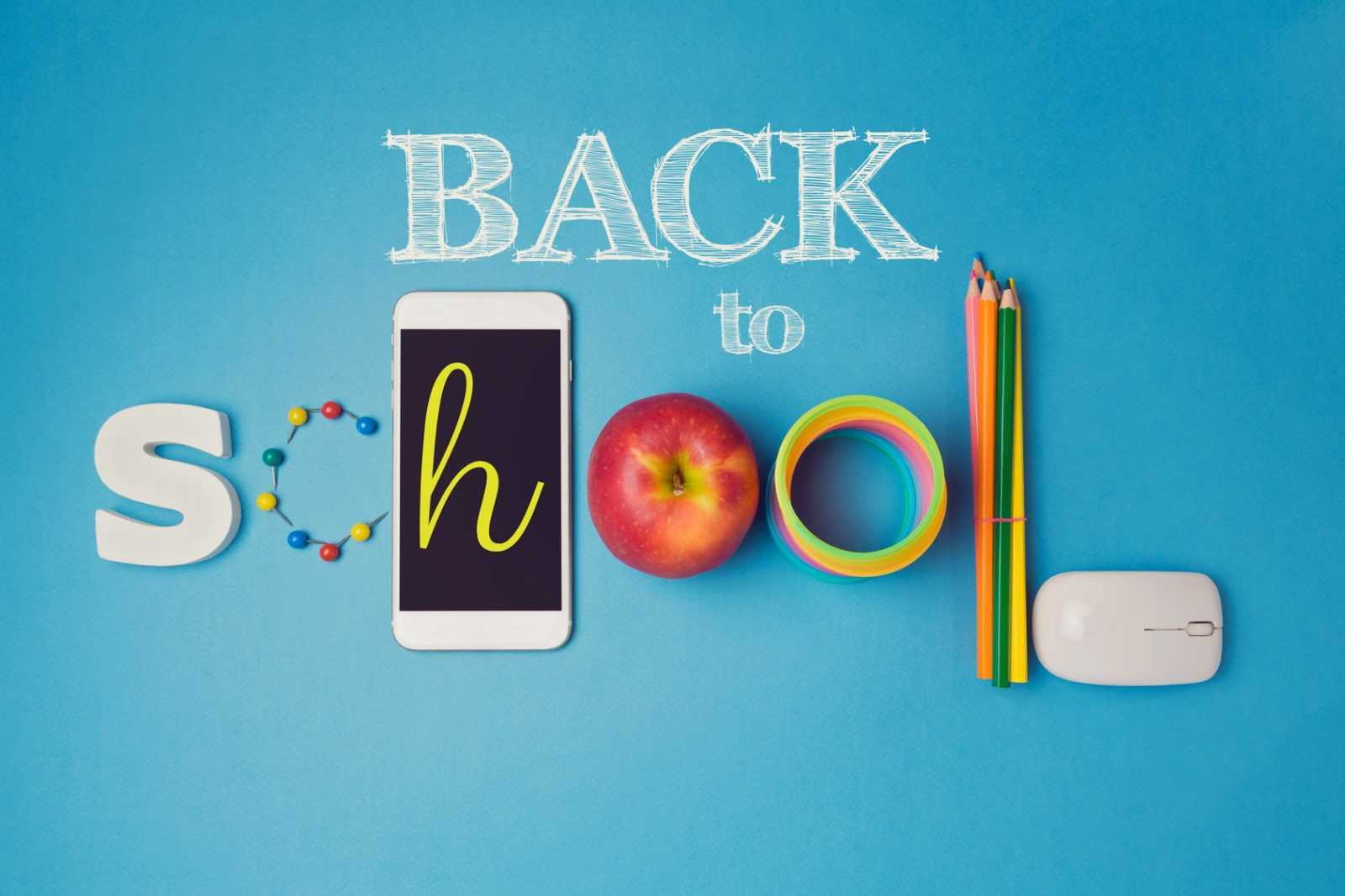 Back to school creative design with smartphone, apple and school supplies. View from above