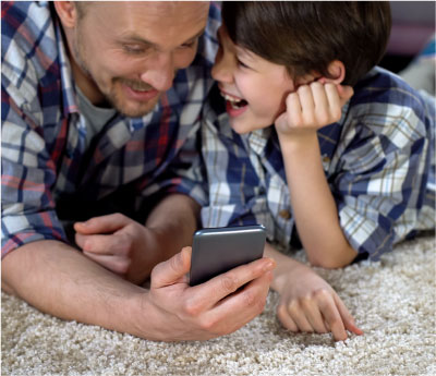 Cheerful-man-and-boy-laughing-after-watching-funny-video-on-smartphone,-joy